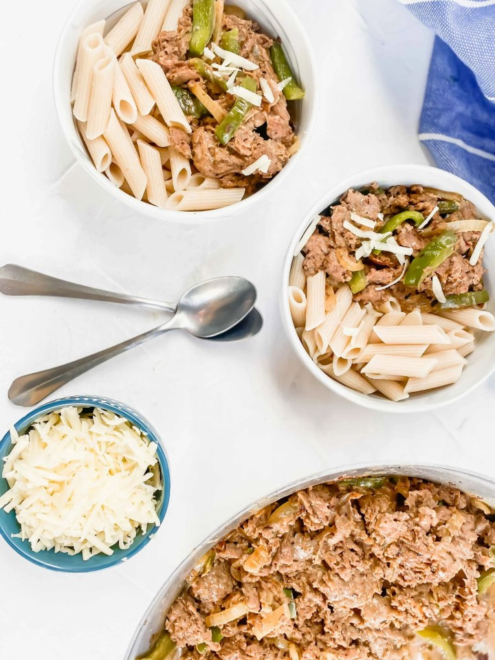 image is two bowls of pasta and cheesesteak with part of the pan and a blue towel.   www.atwistedplate.com/cheesesteak-pasta/