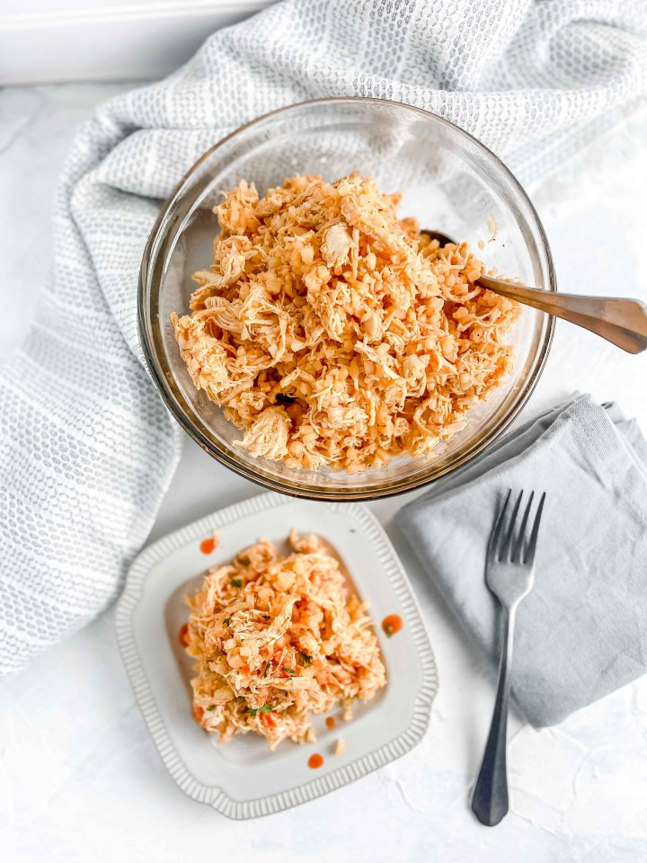 Buffalo Chicken and Cauliflower rice in a bowl with a serving on a plate topped with hot sauce.  there is a fork and napkin next to the plate.  https://www.atwistedplate.com/buffalo-chicken-and-cauliflower-rice/