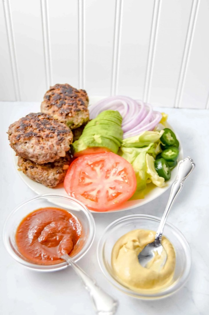 Savory Ranch Burgers with all the fixings, tomato, avocado, lettuce, onion, jalapeño, ketchup and mustard.  www.atwistedplate.com/savory-ranch-burger/