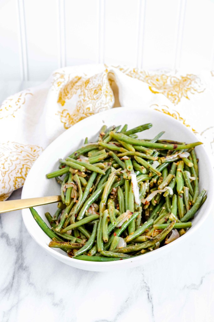 Over view of Spicy Green Beans on a round white bowl with a gold/white towel.   www.atwistedplate.com/spicy-green-beans/