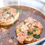 Saucy Pork Chops with Prosciutto. Side angle view of 2 Pork Chops in a sauté pan with sauce and Prosciutto, topped with parsley. www.atwistedplate/saucy-pork-chops/