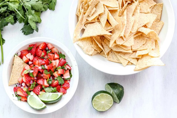 image is a bowl of Strawberry salsa with 2 lime wedges. www.atwistedplate.com/strawberry-salsa/
