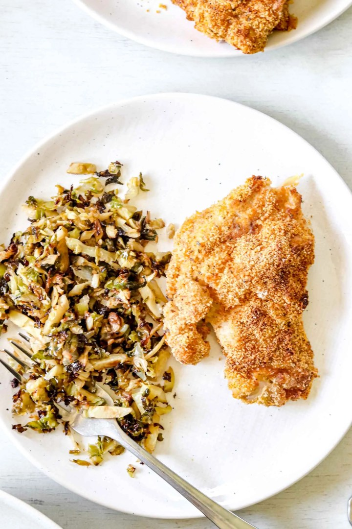 Whole 30 Air-fryer Chicken Thigh Almond flour mixture in a bowl. Image of Whole30 Air-fryer  chicken thigh on a round white plate with onion and garlic Brussel sprouts. https://www.atwistedplate.com/whole30-air-fryer-chicken-thighs/