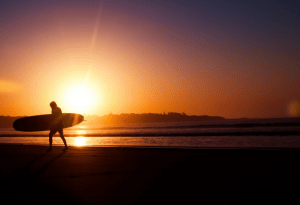 a surfer walking on a beach