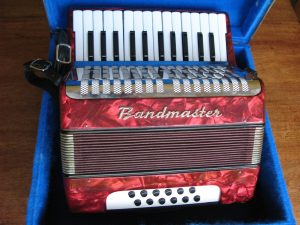 Bandmaster Piano Accordion in marbled red. 26 keys – two octaves, 6 bass and 6 chord buttons. In original case. Leather straps and body in good order. Recently cleaned inside and keys adjusted. Plays well. Made in East Germany