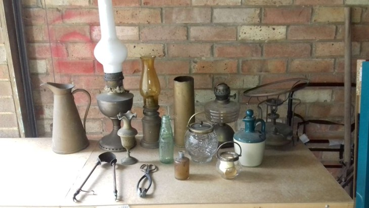 Collection of bottles, jars, oil lamps, jugs, tongs, Primus, shell case