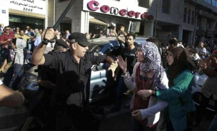 Ein Palästinensischer Polizist greift Demonstranten an. Foto