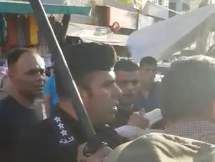 Ein Polizist der Palästinensischen Autonomiebehörde erhebt seinen Schlagstock, als er sich Majdoleen Hassona in Tulkarem nähert. Foto Mohamad Kheiry/Facebook Video Screenshot
