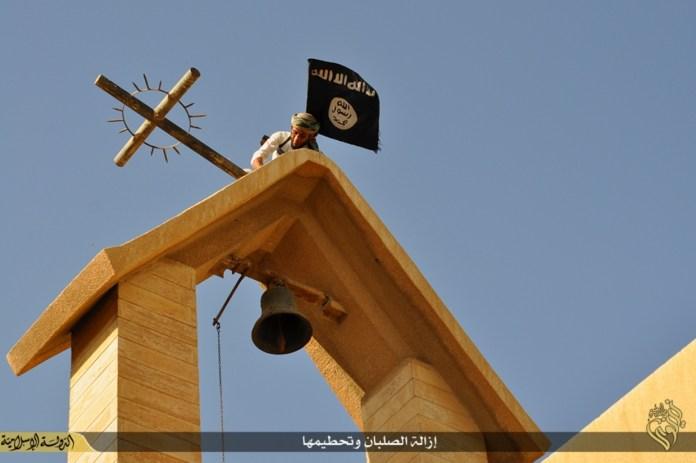 Ein IS-Terrorist ersetzt das Kreuz mit der IS-Flagge über dem St. Georgskloster bei Mosul, Irak. Foto Gates of Nineveh