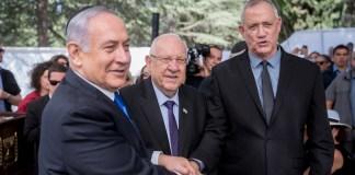 Präsident Reuven Rivlin, Mitte, Premierminister Benjamin Netanjahu, links, und Blau-Weiß-Führer Benny Gantz schütteln sich bei der Gedenkfeier für den verstorbenen Präsidenten Shimon Peres am 19. September 2019 auf dem Herzl-Friedhof in Jerusalem die Hand. Foto Yonatan Sindel/Flash90