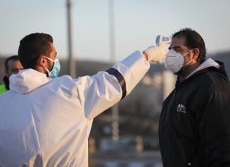 Mitarbeiter des palästinensischen Gesundheitswesens desinfizieren palästinensische Arbeiter, am Eingang des Dorfes Hussan. Foto Nati Shohat/Flash90