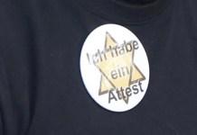 """Davidstern / """"Judenstern"""" mit dem Schriftzug «Ich habe ein Attest»-auf der Brust eines Demonstranten am 21. November an einer Anti-Corona-Massnahmen Kundgebung in Lachen SZ. Foto zVg"""