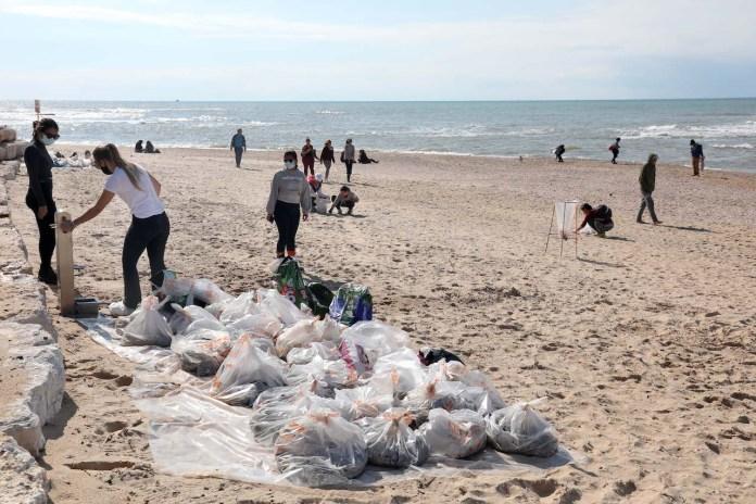 Freiwillige säubern den Strand in Tel Aviv von Teer, nachdem ein Schiff im Mittelmeer Öl freigesetzt und damit einen Grossteil der israelischen Küste verschmutzt hat. 20. Februar 2021. Foto Gideon Markowicz/TPS
