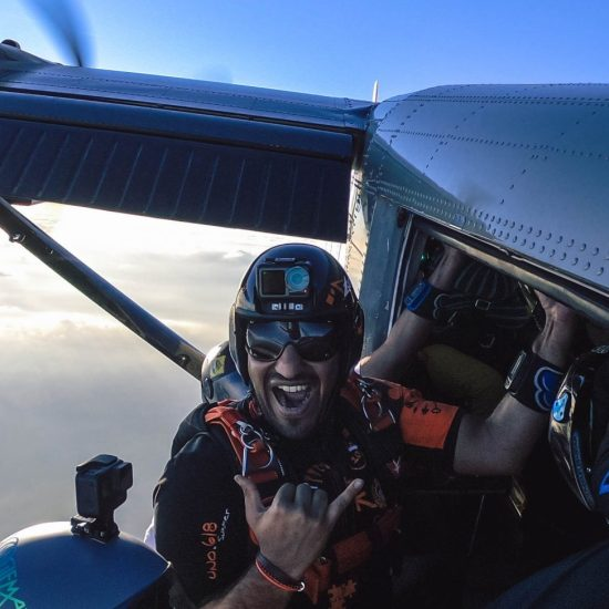 skydiver smiling outside airplane waiting for exit of the group