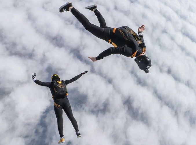 Skydivers flying over clouds with jumpsuit