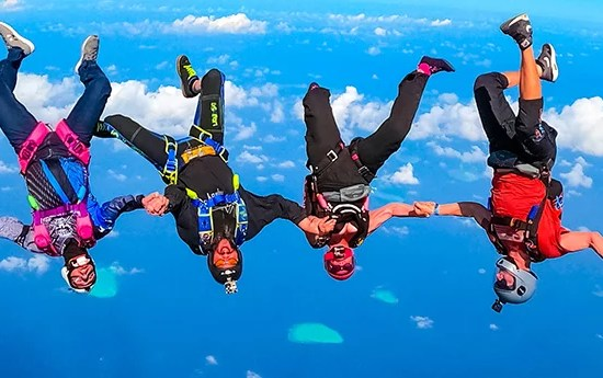 Four friends flying over The Maldives holding hands in free fall