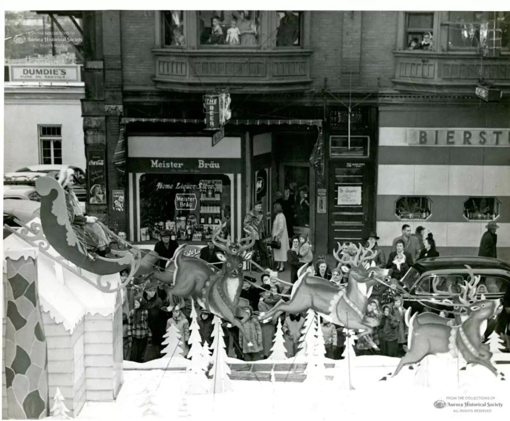 Float from Aurora Christmas Parade travels north on Broadway, north of Benton, passing Home Liquor Store and the Bierstube Bar & Cocktail Lounge, 1949 (Aurora Historical Society photo)