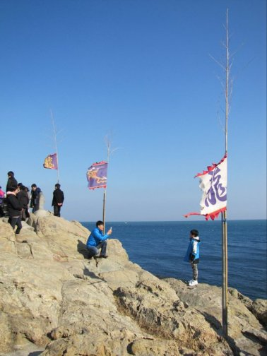 Flags flutter in the wind as we clamber over rocks to see more of Yonggungsa