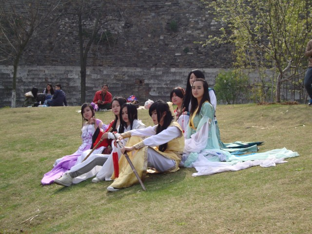 A group of actors in traditional Chinese garb hanging out by the lake.