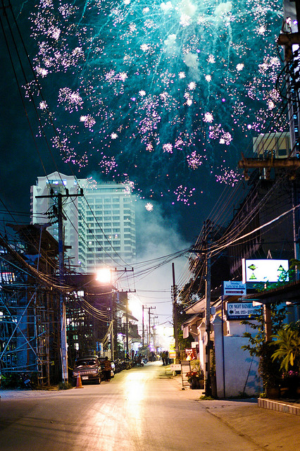 Fireworks blossom like wildflowers over a Chiang Mai street. Photo by Yan Pritzker.