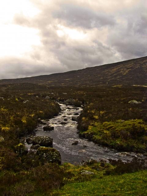 A brook under stormy skies in Glencoe, Scotland.