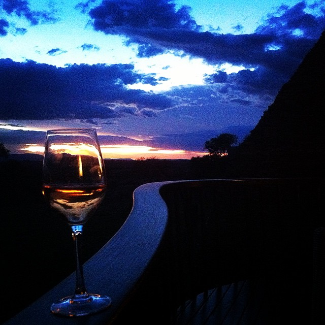 A glass of wine, a sunset, and one very happy traveler.