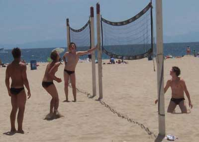 Boys is speeods playing beach volleyball.