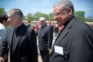 Cardinal Blase Cupich, left, walks with Bishop Joseph Perry while attendees sit and listen to speakers. | ALEXA ROGALS/Staff Photographer
