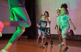 Children climb up to the stage and start dancing to music together on Friday, during the annual Exclusive Spring Fashion Show inside the auditorium at Ella Flagg Young Elementary School in Chicago's Austin neighborhood. | Photos by ALEXA ROGALS/Staff Photographer