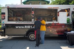 Attendees try out some barbecue from Robinson's No. 1 Ribs food truck last Saturday, during the West Side's Juneteenth Celebration at Garfield Park. | ALEXA ROGALS/Staff Photographer