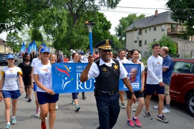 RALLY FOR PEACE: 15th District Police Commander Ernest Cato carries the torch during the Chicago leg of the Sri Chinmoy Oneness-Home Peace Run in Austin on July 12. | YATKARA ALEKSA-POLSKYV/Contributor
