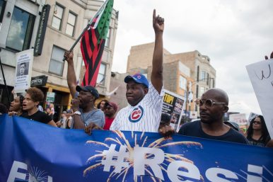 Rev. Ira Acree of Greater St. John Bible Church in Chicago's Austin neighborhood, holds up a sign and marches down Clark Street towards Wrigley Field on Thursday during an anti-violence protest in Chicago. | ALEXA ROGALS/Staff Photographer