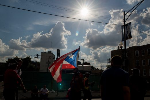 A marcher walks down Clark Street holding up a Puerto Rican flag on Thursday, during an anti-violence protest in Chicago. | ALEXA ROGALS/Staff Photographer