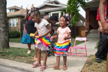Residents sit on the curb outside of their homes while cheering and grabbing thrown candy last Saturday, during Congressman Danny Davis' annual Back 2 School parade on Central Avenue in Chicago's Austin neighborhood. | Photos by ALEXA ROGALS/Staff Photographer