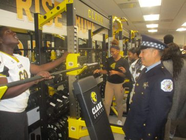 THAT'S WHAT'S UP: What Michelle Clark High School students marvel at their new fitness equipment inside of the school's weight room, which is named after a beloved resource officer who died. A Chicago Police officer looks on. | IGOR STUDENKOV/Contributor