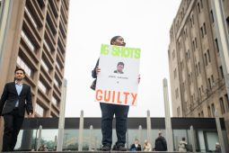 "Rena Shepherd, of Chicago, holds up a sign at the top of the courthouse steps that reads, simply: ""16 Shots. Jason Van Dyke is Guilty."" 