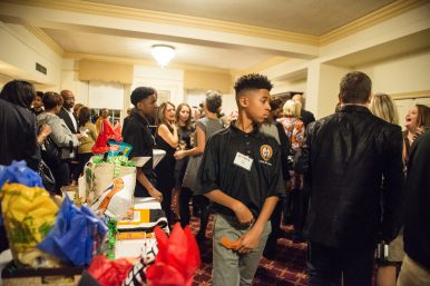 Room to Grow: Guests look over the items in the silent auction while enjoying drinks and appetizers before dinner during the YEMBA 10th year anniversary celebration at Nineteenth Century Club in Oak Park. | ALEXA ROGALS/Staff Photographer