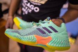 Co-owner Darris Kelly holds up a pair of specialty Adidas at Flee Club shoe store on Western Avenue in Chicago's Near West Side neighborhood. | ALEXA ROGALS/Staff Photographer