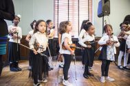 Coming together: Students line up for their violin and cello performances on Dec. 8, 2018, during the Westside Instructional String and Harp Program's Holiday Recital at the Garfield Park Fieldhouse in Chicago. Family members and friends watch and cheer as students perform their piano solos. | ALEXA ROGALS/Staff Photographer