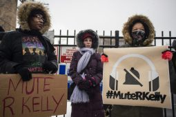 Sharita Galloway, left, and Christina Waters, both of Oak Park, hold up signs across the street on Saturday, Jan. 12, during a Mute R. Kelly protest outside of his studio on Justine Street in Chicago.. | ALEXA ROGALS/Staff Photographer
