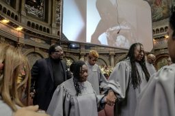 PRAYERS OF PROTECTION: Rev. Marshall Hatch (wearing black in photo at top left) prays with congregants during the Feb. 24 unveiling service for the Sankofa Peace Window. | SEBASTIAN HIDALGO/Contributor