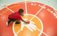A player from Team St. Paul scoops up the bean bag in the middle of the court, which is worth the most point points, on Saturday, March 9, during the Community Works and Sports Alternative Youth Olympics event at the By The Hand Club For Kids in Austin.   ALEXA ROGALS/Staff Photographer