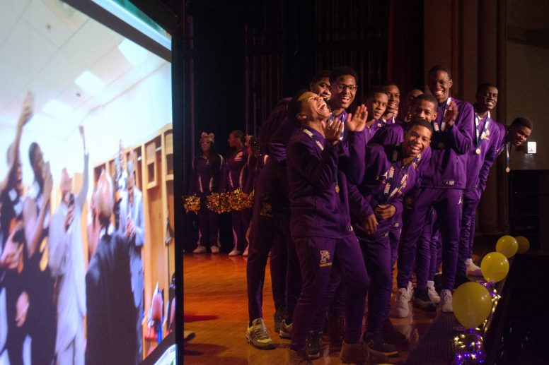 The Providence St. Mell Knights look at a homemade video of their IHSA State Championship celebration during a prep rally at Providence St. Mell High School, on the Westside of Chicago. The Knights haven't won a state trophy since 1984-1985. | SEBASTIAN HIDALGO/Contributor