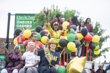 It's a party ...: Parade participants sit on a float and wave flags and cheer last Saturday, during the fifth annual African-American Awareness and Appreciation Parade Juneteenth Celebration on Madison Street on the West Side. | ALEXA ROGALS/Staff Photographer
