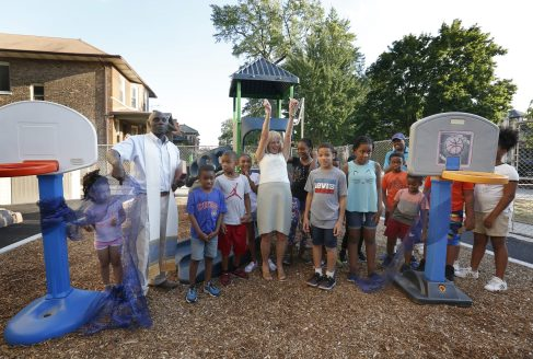 A BIG DEAL: St. Catherine-St. Lucy Principal Sharon Lemy, center, is surrounded by students and Father George Omwando during the Aug. 7 ribbon-cutting for the school's new playground. | Archdiocese of Chicago