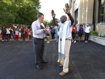 Fr. George Omwando, pastor at the parish blesses the new playground with school families Aug. 7 prior to a ribbon cutting ceremony for their new playground at St. Catherine St. Lucy School, 27 Washington Blvd in Oak Park. Holding the book is Tom Zbierski, Senior Director, Scholarship Programs and School Relations for Big Shoulders Fund. The school received a donation from Enchanted Backpack and Big Shoulders to complete the first playground in the school's history. | Archdiocese of Chicago