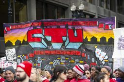 Demonstrators hold up signs on Thursday, Oct. 17, during a Chicago Teachers Union rally in the Chicago Loop. | ALEX ROGALS/Staff Photographer