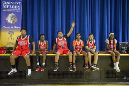 A group of kids from the Garfield Park league watch a scrimmage on Dec. 19, during youth basketball training from the Chicago Westside Police at Genevieve Melody Public School in Chicago. | ALEX ROGALS/Staff Photographer