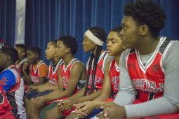 A group of players from the Garfield Park AAU basketball team watch a scrimmage game on Dec. 19, during youth basketball training from the Chicago Westside Police at Genevieve Melody Public School in Chicago. | ALEX ROGALS/Staff Photographer