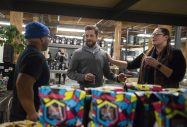 Cool beans: Owner and founder Joshua Millman, middle, talks with guests at the new roastery for Passion House Coffee and Roasters in East Garfield Park. | ALEX ROGALS/Staff Photographer